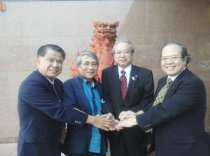 シーサーの前で沖縄県医師連盟の先生方と握手する羽生田たかしの写真